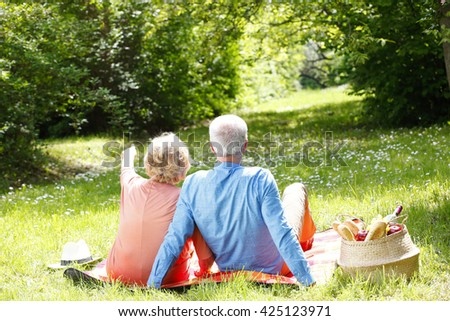 Rear view of an elderly woman and a senior man sitting on the blanket while relaxing outdoor. - stock photo