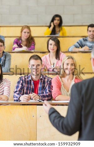 Rear view of an elegant teacher with students sitting at the college lecture hall - stock photo