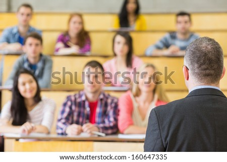 Rear view of an elegant teacher with students sitting at the college lecture hall