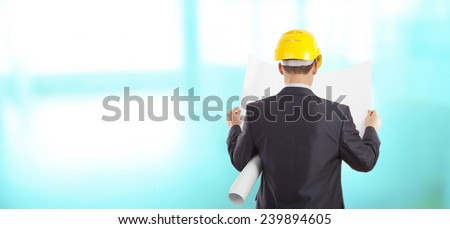 Rear view of architect looking comparing blue print paper plan housing project with building wearing yellow helmet Back view businessman on wall and  window background Empty copy space for inscription - stock photo