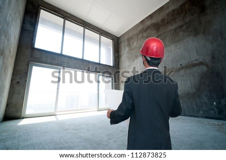 Rear view of architect looking comparing housing project with building - stock photo