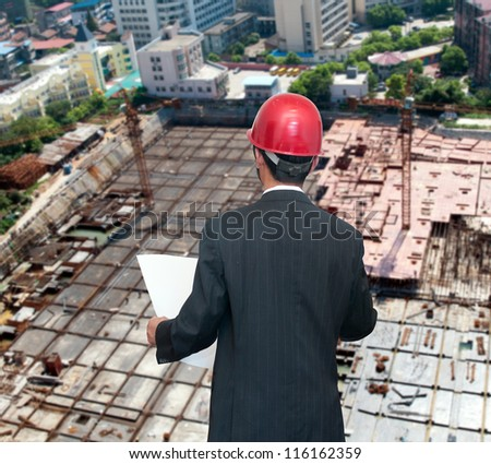 Rear view of architect looking comparing housing project with building