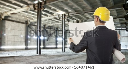 Rear view of architect looking comparing housing project with building paper plan  - stock photo
