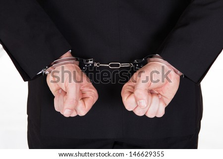 Rear view of arrested businessman with handcuffs - stock photo
