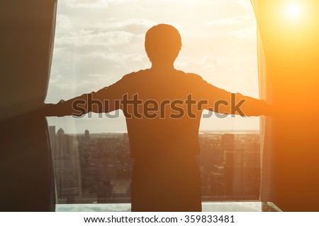 Rear view of Asian businessman draw the curtain in office. - stock photo