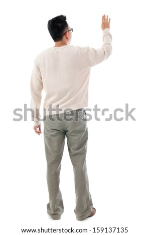 Rear view of Asian man hand touching on transparent virtual screen, space for text/button, full length standing isolated on white background.