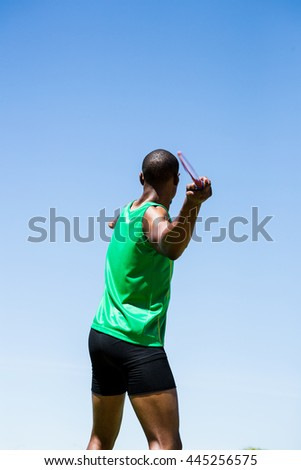 Rear view of athlete about to throw a javelin in the stadium