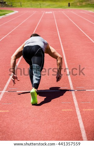 Rear view of athlete running on the running track on a sunny day - stock photo