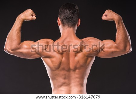 Rear view of athletic man is showing muscles of the back and hands on a dark background.