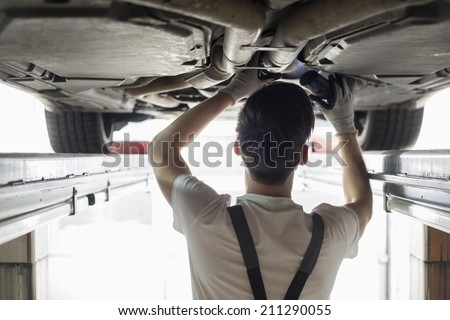 Rear view of automobile mechanic examining car in workshop - stock photo