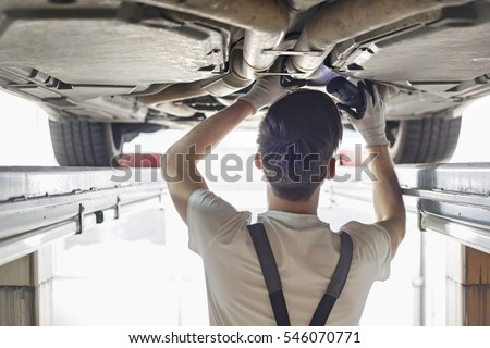 Rear view of automobile mechanic examining car in workshop