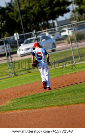 Rear view of baseball player walking across field during game. - stock photo