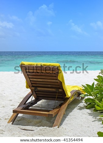 rear view of beach chair in front of turquoise ocean