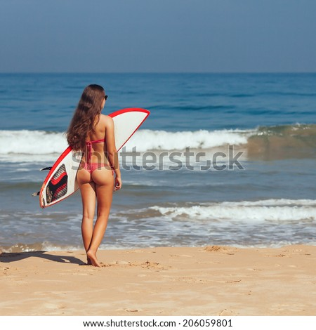Rear view of beautiful sexy young woman surfer girl in bikini with white surfboard on a beach - stock photo