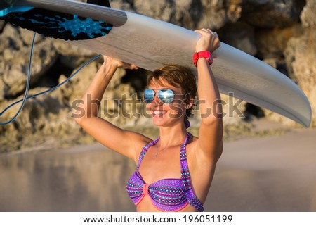 Rear view of beautiful sexy young woman surfer girl in bikini with white surfboard on a beach at sunset or sunrise - stock photo