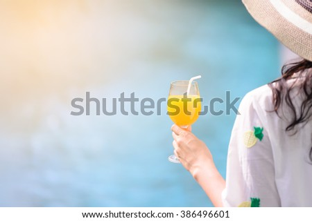 Rear view of beautiful woman in hat is holding orange juice glass at poolside in summer. - stock photo