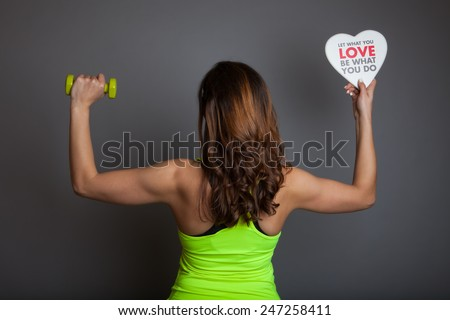 """Rear view of beautiful young fitness model (bodybuilder) woman training with dumbbell (weight) and holding a white heart shape with """"Let What You LOVE Be What You Do"""" text on grey background - stock photo"""