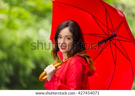 Rear view of beautiful young woman in red raincoat holding red umbrella. She is looking at camera over the shoulder and smiling while walking in the park on rainy day. - stock photo