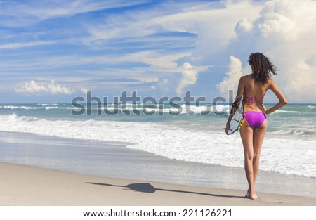 Rear view of beautiful young woman surfer girl in bikini with surfboard standing in the surf on a beach  - stock photo