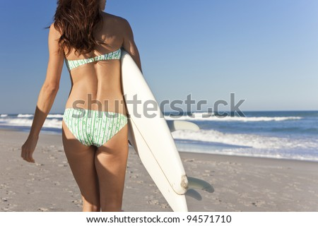 Rear view of beautiful young woman surfer girl in bikini with white surfboard at a beach
