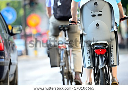 Rear view of bicyclist with child chair - stock photo