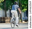 Rear view of bicyclist with helmet - stock photo
