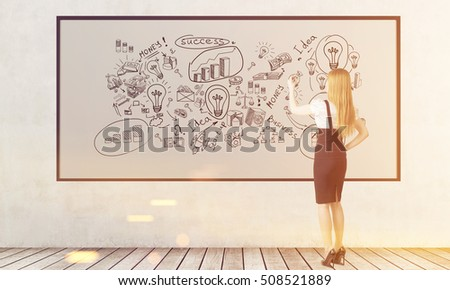Rear view of blond woman who is drawing business sketches on whiteboard. Concept of business education. Toned image