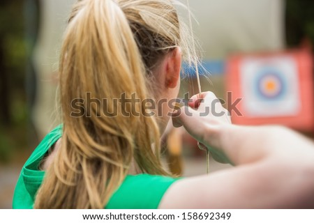 Rear view of blonde about to shoot arrow in the archery range - stock photo