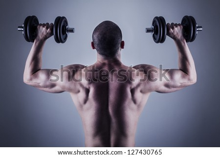 Rear view of bodybuilder training with dumbbells. Back muscles - stock photo