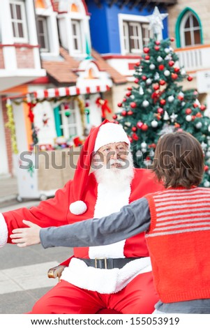 Rear view of boy and Santa Claus about to embrace in courtyard - stock photo