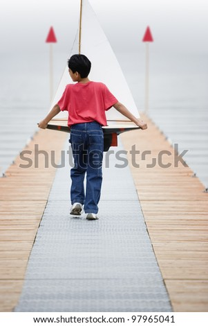 Rear view of boy walking down pier holding toy sailboat - stock photo