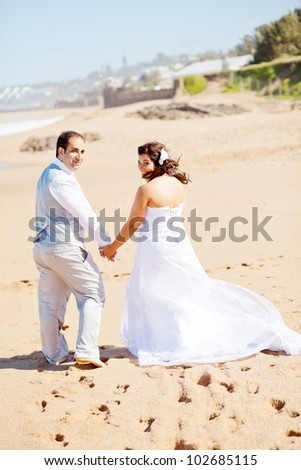 rear view of bride and groom walking on beach - stock photo