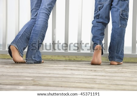Rear view of brother and sister's legs as they stand on on the boardwalk. Horizontal shot.