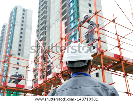 Rear view of builder inspector checking a construction site works. - stock photo