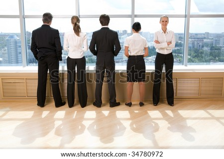 Rear view of business group standing in row and looking through window with their leader smiling at camera - stock photo