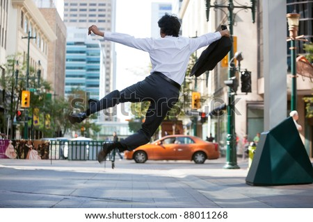 Rear view of business man jumping in air and kicking heals - stock photo
