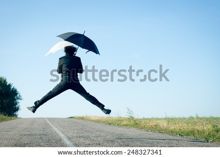 Rear view of business man jumping legs split with two umbrellas on the road - stock photo