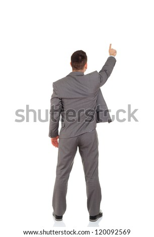 Rear view of business man pointing finger at copy space isolated over white background, full length portrait of businessman standing back - stock photo