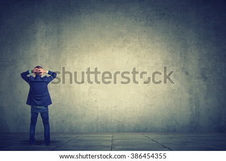 Rear view of business man standing in front of a wall hands on head wondering what to do next. Full length of businessman facing the wall  - stock photo