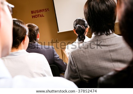 Rear view of business people listening attentively while sitting at conference - stock photo