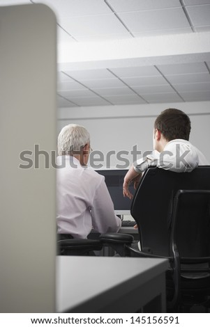 Rear view of business people using computer in office cubicle - stock photo