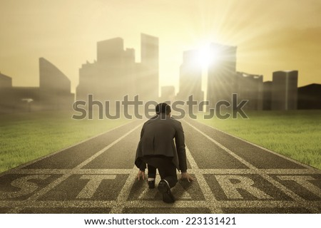 Rear view of business person in ready position on start line to compete - stock photo