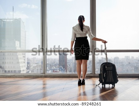 Rear view of business woman holding suitcase - stock photo