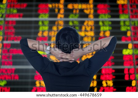 Rear View of business woman looking at stock market board.