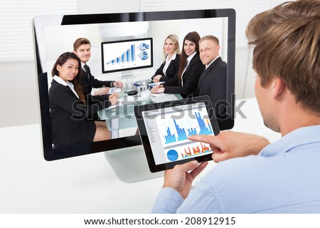 Rear view of businessman analyzing graphs on computer while video conferencing in office