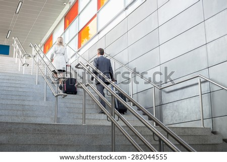 Rear view of businessman and businesswoman with luggage moving upstairs in railroad station - stock photo