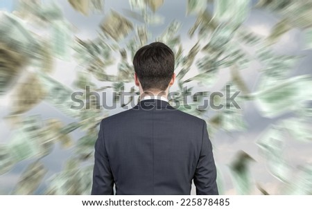 Rear view of businessman and falling dollars over the sky background. - stock photo