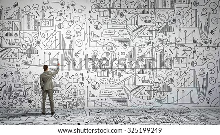 Rear view of businessman drawing business sketch on wall - stock photo