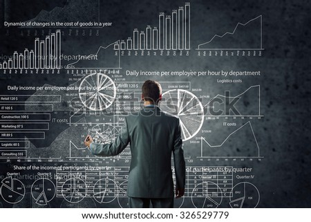 Rear view of businessman drawing chalk business sketches on wall - stock photo