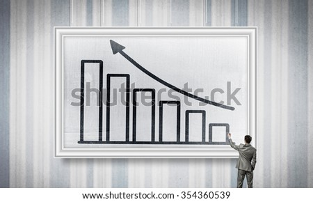 Rear view of businessman drawing growing arrow on white banner